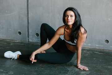 young brunette fitness woman sitting on floor in brutal concrete gym