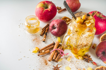 Autumn healthy breakfast idea. Overnight oatmeal in a mason jar with spiced honey apple, spices and...