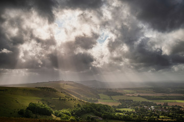 Foto op Canvas Donkergrijs Stunning Summer landscape image of escarpment with dramatic storm clouds and sun beams streaming down