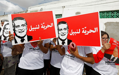 Supporters of Nabil Karoui carry his pictures ahead of parliamentary elections in Tunis