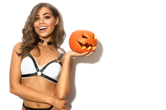 Sexy girl with Halloween pumpkin in white underwear and black leather harness on white isolated background
