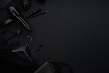 Black monochromatic flatlay on black background. Clothes, accessories and beauty equipment. Black friday sale concept. Copy space