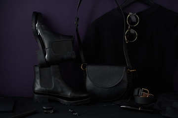 Fashion accessories, chelsea boots, leather bag and t-shirt dress arranged in dark-coloured still life composition