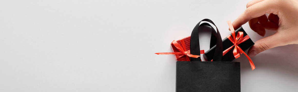 cropped view of woman putting small gift boxes in black shopping bag on white background, panoramic shot
