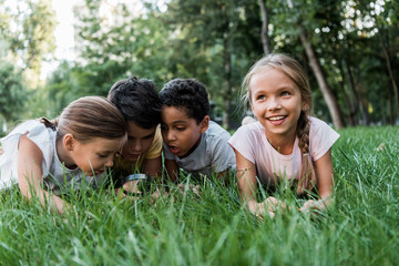 selective focus of cute multicultural children looking at green grass though magnifier Wall mural