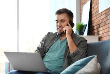 Young man talking on phone while using laptop in living room