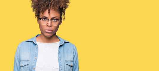 Beautiful young african american woman wearing glasses over isolated background skeptic and...