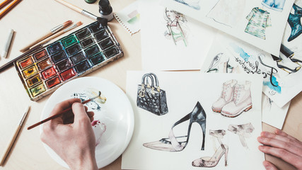 Fashion sketching. Women clothing design. Male artist painting with watercolors.