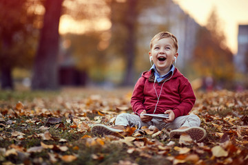 Smiling boy listen music on smartphone. Family, childhood, season and people concept..