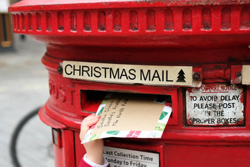 Child is posting a letter for Santa Claus into the Christmas english postbox. Popular children Christmas activity.