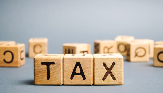Wooden blocks with the word Tax. Business and finance concept. Taxes and taxation. The tax burden