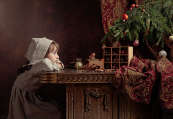Little girl in an vintage linen dress dreaming near the table with sweets. Genre portrait in retro style.