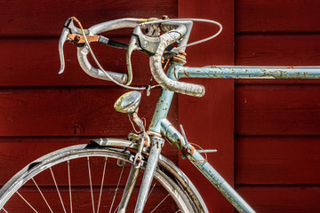 An old, blue and rusty racing bike leaning against a red, wooden wall.
