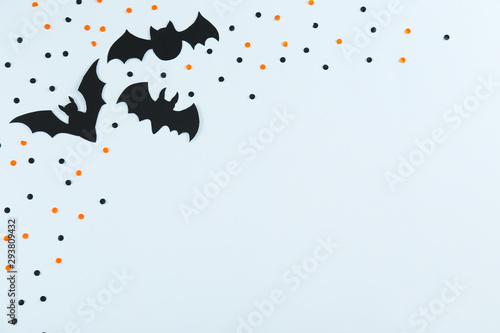 Halloween themed flat lay composition with decorative bats, on dark paper textured background with a lot of space for text. Close up, top view.