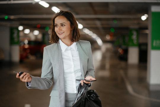 Businesswoman on parking locking car