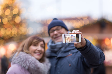 technology, winter holidays and people concept - happy senior couple taking selfie by smartphone at christmas market on town hall square in tallinn, estonia