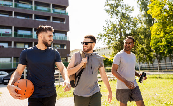 sport, leisure games and male friendship concept - group of men or friends going to play basketball outdoors