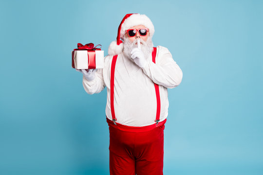 Hush its secret. Portrait of focused funny funky fat santa claus with big abdomen belly prepare gift for eve noel hold small giftbox wear red pants suspenders isolated over blue color background