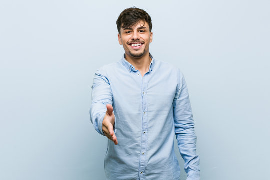 Young hispanic business man stretching hand at camera in greeting gesture.