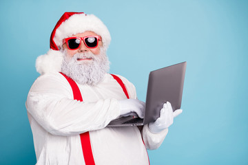 Close up photo of funny funky overweight santa claus in hipster sunglass use laptop search...