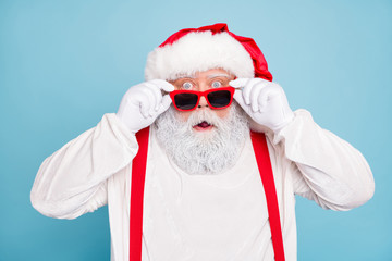 Close up photo of impressed fat overweight santa claus stare in modern eyeglasses look funny funky hear wonder christmas seasonal discounts wear suspenders overalls isolated over blue color background