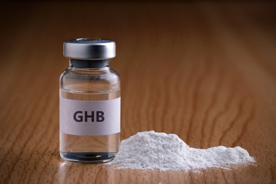 Bottle of GHB with drug powder on wooden background.GHB