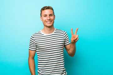 Young caucasian man against a blue wall showing victory sign and smiling broadly.