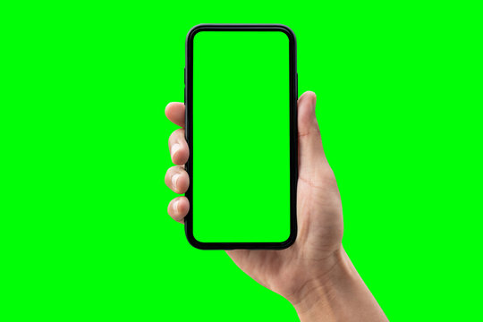 Hand holding smartphone isolated on green background.