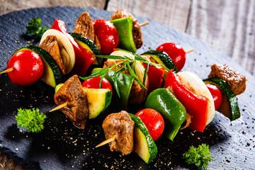 Foto op Plexiglas Groenten Grilled shashliks with meat on black stone plate