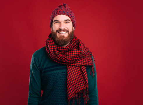 Simple portrait of smiling handsome bearded man who is wearing scarf and winter hat on red background.