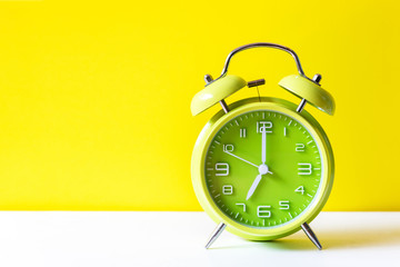 Alarm green vintage alarm clock falling on the floor with color background. Morning and Start up Concept