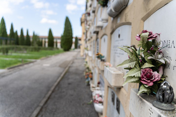 Stock photo of a discoloured plastic flowers in the tomb with the cemetery out of focus in the background