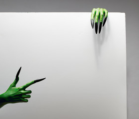 Halloween concept. Two green hands hold blank gray sheet of paper in studio.