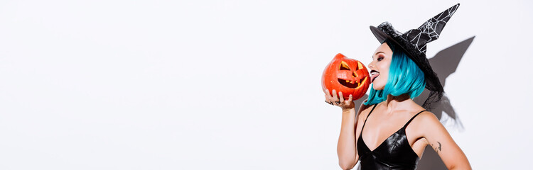 panoramic shot of sexy girl in black witch Halloween costume with blue hair licking spooky carved pumpkin on white background
