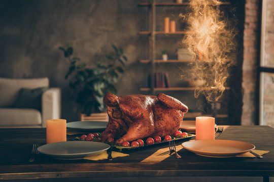 Close up photo of big baked roast beef turkey in middle of holiday festive table empty plates and two candles around in living room without people indoors
