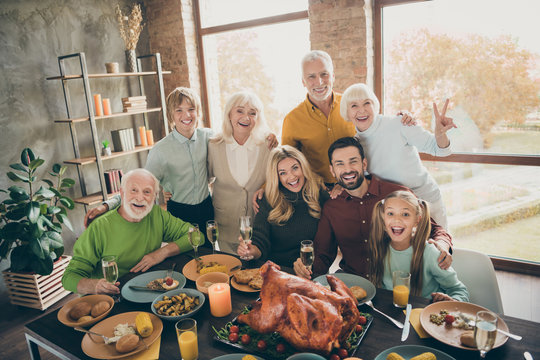 Photo of big family standing hugging feast table holiday roasted turkey making portrait relatives multi-generation raising wine glasses show v-sign in living room indoors