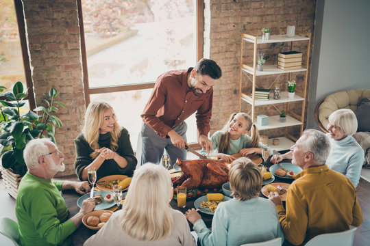 Photo of big family sit feast meals table around holiday roasted turkey father guy making slices hungry relatives waiting turn evening party in living room indoors