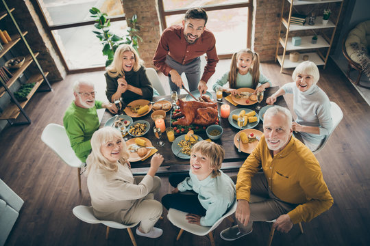 High angle above view photo of big family sit feast meals table roasted turkey father guy making slices multi-generation relatives evening in living room indoors