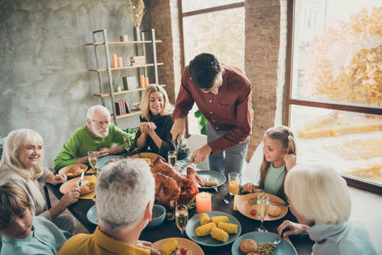 Photo of big family sit feast meals table around roasted turkey father guy making slice for little daughter hungry relatives waiting evening party in living room indoors