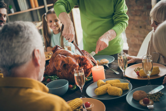 Cropped photo of full family sit feast dishes table near roasted turkey grandpa cutting meat into slices hungry relatives waiting excited beginning in living room indoors