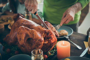Cropped photo of family feast roasted turkey on table grandfather hands cutting meat into slices hungry relatives waiting in living room indoors