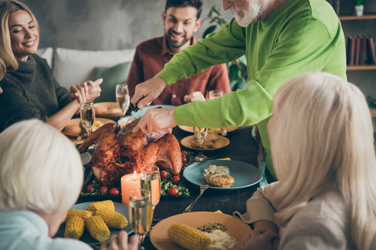 Cropped photo of full big family sit feast dishes table around roasted turkey grandfather cutting meat into slices hungry relatives waiting excited in living room indoors