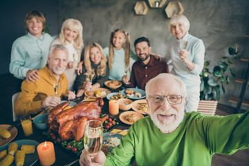 Photo of big family sit hugging feast dishes table around roasted turkey multi-generation relatives making group selfies raising wine glasses in living room indoors