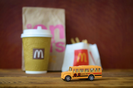 Small school bus and McDonald's junk food on wooden table