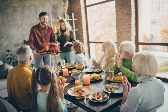 Photo of full family reunion sit feast dishes table wife husband hold big roasted turkey clap hands multi-generation eight relatives annual event in living room indoors