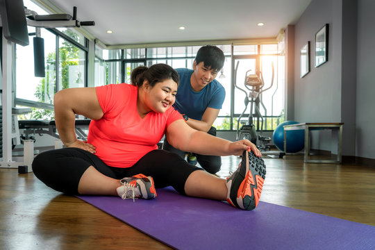 Two Asian trainer man and Overweight woman exercising stretch together in modern gym, happy and smile during workout. Fat women take care of health and want to lose weight concept..