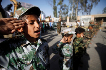 A boy salutes the flag as he and supporters of the Houthi movement attend a rally to celebrate following claims of military advances by the group near the borders with Saudi Arabia, in Sanaa