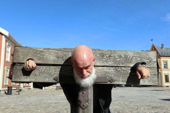 Bearded, bald man in a pillory, Old Town, Fredrikstad, Norway