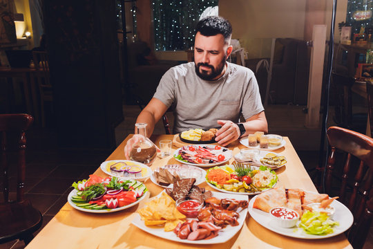 man drinks vodka at a large table with food and snacks.