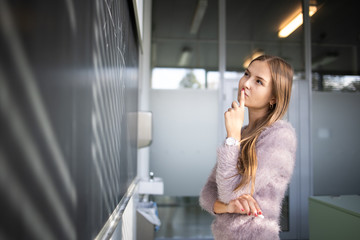 Pretty, young female student in front of a blackboard during math class